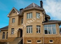 Облицовка фасада частного дома из бежевого дагестанского ракушечника в сочетании с мекегинским доломитом цокольной части