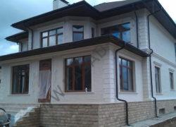 Облицовка коттеджа дагестанским камнем. Отделка цоколя дома диким камнем,  фасад из белого известняка.